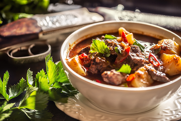 Deer stew in a bowl hunting weapon as a decoration.